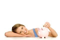 Woman putting money in piggy bank Royalty Free Stock Image
