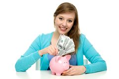 Woman putting money in piggy bank Stock Image