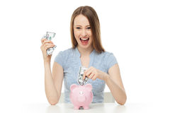 Woman putting money in piggy bank Stock Photos