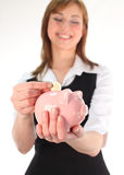 Woman putting money in a Piggy Bank. In a time of recession Royalty Free Stock Photos