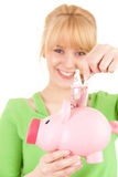 Woman putting money into pink piggy bank Stock Photos