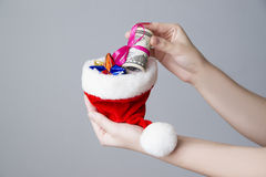 Woman putting money in a Santa hat on gray background Royalty Free Stock Photo