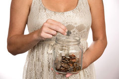 Woman Putting Money In Savings Jar. Woman puts a quarter in a clear glass savings jar for use as a financial and banking concept Stock Images