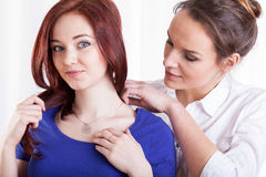 Woman putting necklace on her sister's neck Stock Photos