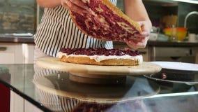 Woman putting next sponge cake. Home baking. Sponge cake lies on turn table stock footage