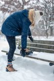 Woman putting non slip snow cleats on boots for winter hike royalty free stock image