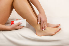 Woman putting ointment on bad ankle applying cream Royalty Free Stock Image