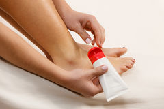 Woman putting ointment on bad ankle applying cream Stock Photos