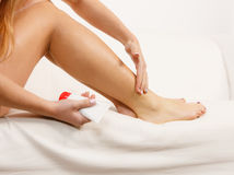 Woman putting ointment on bad ankle applying cream Royalty Free Stock Photos