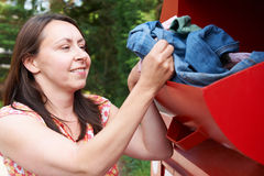 Woman Putting Old Clothes Into Recycling Bank Royalty Free Stock Images