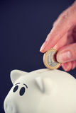 Woman putting one euro coin in piggy bank Royalty Free Stock Images