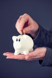 Woman putting one euro coin in piggy bank. Money savings and home budget concept Royalty Free Stock Image