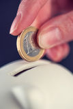 Woman putting one euro coin in piggy bank. Money savings and home budget concept, macro close up of fingers Royalty Free Stock Images