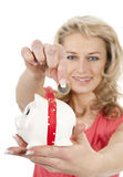 Woman putting one euro coin in piggybank Royalty Free Stock Photography