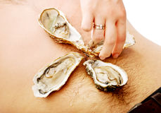 Woman putting oysters on man's belly. Royalty Free Stock Image