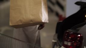 Woman putting packages with purchases in car trunk. Midsection of female in summer dress putting purchases in paper bags from shopping cart into car trunk. Adult stock video footage