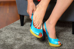 Woman putting on a pair of trendy blue shoes Royalty Free Stock Photos