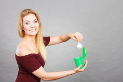 Woman putting paper into small trash can Royalty Free Stock Photos