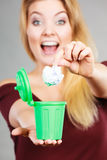 Woman putting paper into small trash can Royalty Free Stock Photo