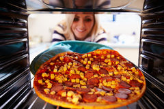 Woman Putting Pepperoni Pizza Into Oven To Cook royalty free stock image