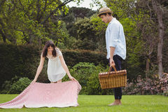 Woman putting picnic blanket in garden. And men standing with picnic basket Stock Photo