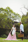 Woman putting picnic blanket in garden. And men standing with picnic basket Stock Photos