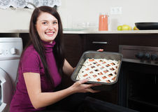 Woman putting  pie on  pan into oven Royalty Free Stock Photos