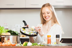 Woman putting pieces lemon to fish  in frying pan Royalty Free Stock Photography