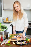 Woman putting pieces of saltwater fish into frying pan Stock Images