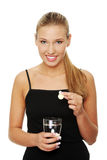 Woman putting pill into glass full of water Stock Photography