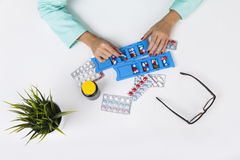 Woman is putting pills in a container. Top view of woman doctor putting pills in blue container. A plant is standing on her desk Royalty Free Stock Photography