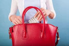 Woman putting pills to red leather handbag royalty free stock photography