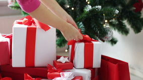 Woman putting present under christmas tree stock footage