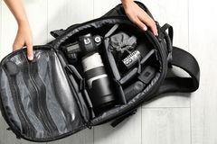 Woman putting professional photographer`s equipment into backpack on floor stock photo