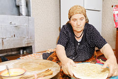 Woman putting raw bread on board Royalty Free Stock Photo