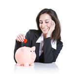 Woman putting a red hearth  into a piggy bank Stock Photography