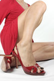 Woman putting on red heels Stock Images
