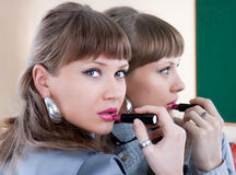 Woman putting on a red lipstick in a mirror Royalty Free Stock Photos