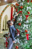 Woman Putting Ribbon Bow on Christmas Tree stock images