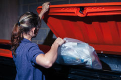 Woman putting rubbish in bin. A young woman is putting a bag of rubbish in a large bin at night Stock Photography