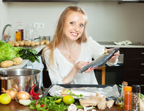 Woman putting  saltwater fish into sheet pan Royalty Free Stock Images