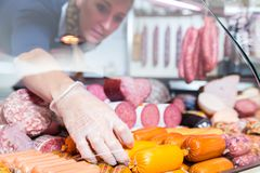 Woman putting sausages and meat in butcher shop display royalty free stock photo