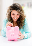 Woman putting savings in a piggybank Stock Image