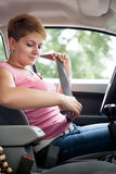 Woman putting seat belt Stock Photography
