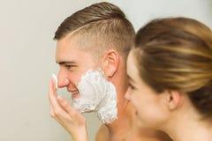 Woman putting shaving foam on boyfriends face Stock Image