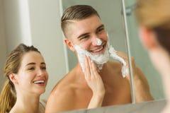 Woman putting shaving foam on boyfriends face Stock Photos