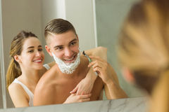 Woman putting shaving foam on boyfriends face Royalty Free Stock Photos
