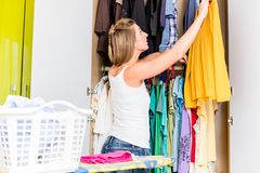 Woman putting shirt after laundry back into wardrobe Stock Photos