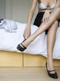 Woman Putting On Shoes In Bed Stock Photo
