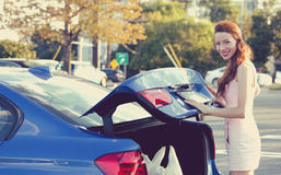 Woman putting shopping bags inside car trunk Stock Images